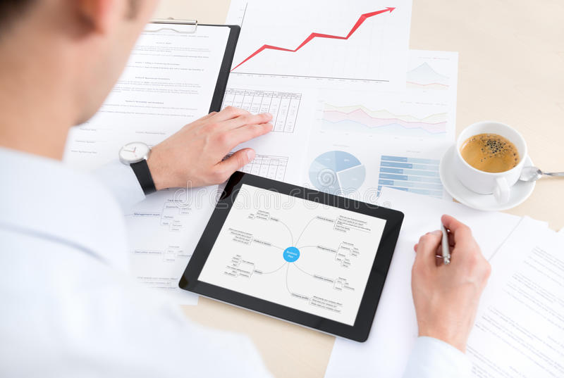 Businessman at the workplace. Working with documents and using modern digital tablet