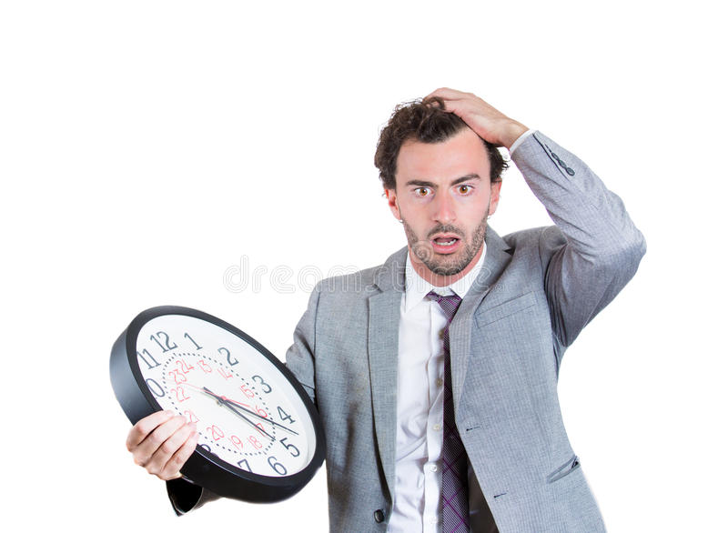 A businessman worried that he is running out of time. A close-up portrait of a businessman, executive, leader holding and looking anxiously at a clock, stressed stock image