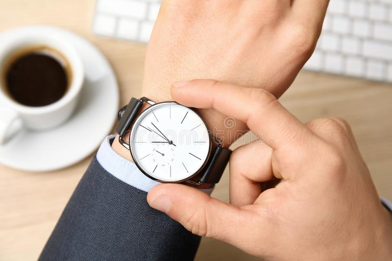 Businessman with wrist watch working at office table, closeup. Time management stock photography