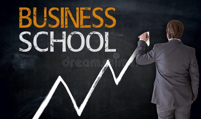 Businessman writes business school on blackboard concept.  royalty free stock image