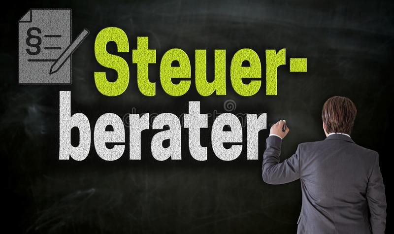 Businessman writes with chalk Stuerberater in german tax consultant on blackboard.  stock image