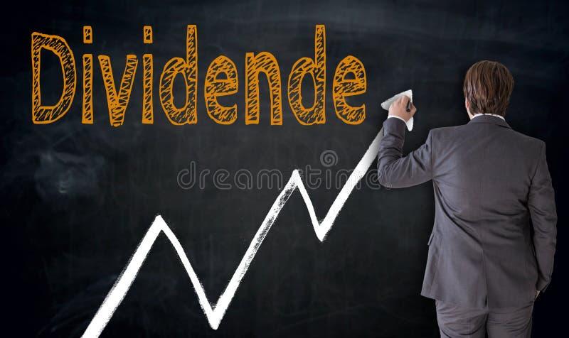 Businessman writes Dividende in german dividend on blackboard. Concept stock photography