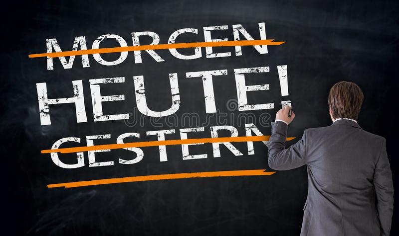 Businessman writes in german Today, Yesterday, Tomorrow on black royalty free stock image