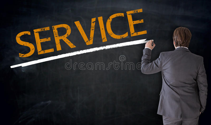 Businessman writes service on blackboard concept royalty free stock photography