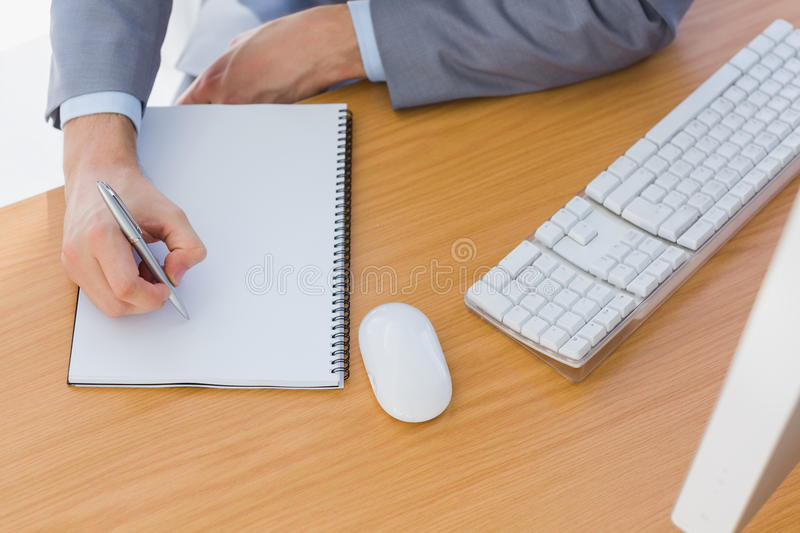 Businessman writing on blank notepad stock images
