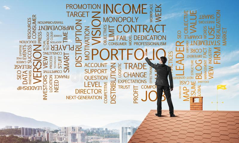 Young businessman standing on house roof and writing leadership skill concept. Mixed media royalty free stock image