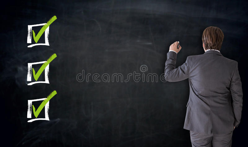 Businessman writing with checkbox concept on blackboard royalty free stock image