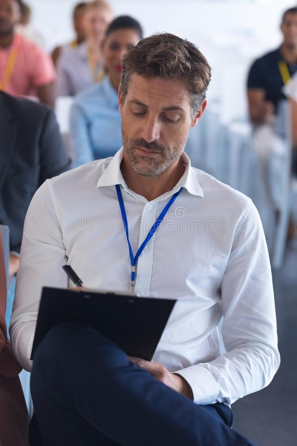 Businessman writing on clipboard in a business seminar stock photos