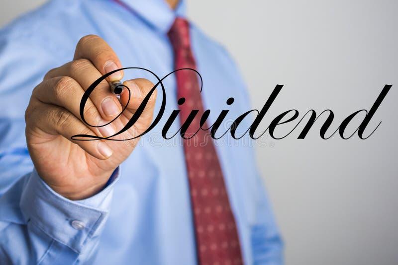 Businessman writing Dividend word on virtual screen.  stock photos