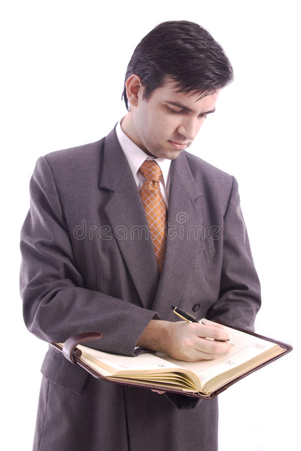 Businessman writing in his agenda. Businessman writing something important in his agenda isolated over white background royalty free stock photos