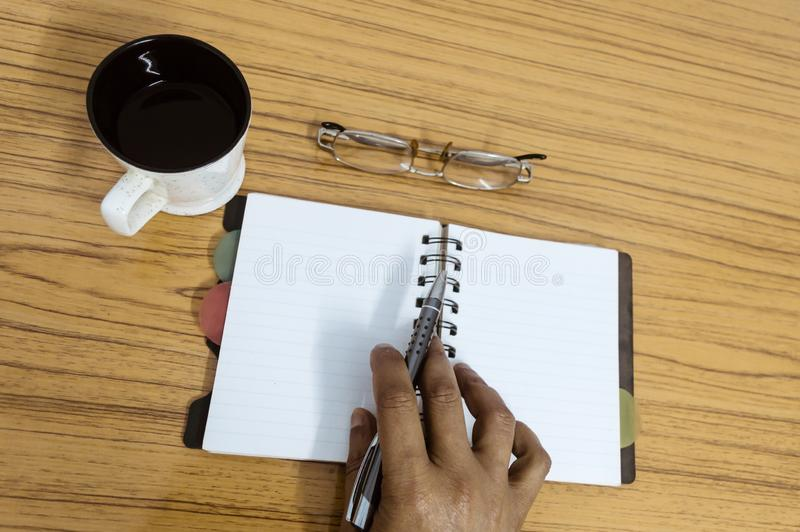 Businessman writing in his diary. Open notebook with blank pages next to cup of coffee and eyeglasses on wooden table. Business royalty free stock photo