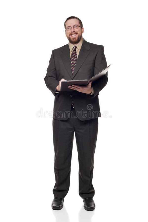 Businessman writing on notepad. Isolated full length studio shot of the front view of a businessman writing on notepad and smiling while looking at the camera stock photos