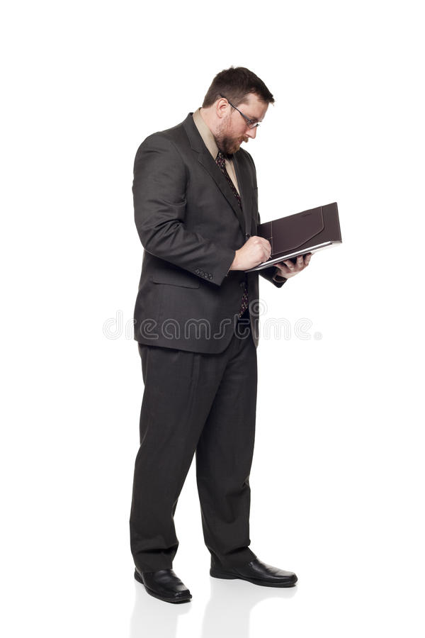 Businessman writing on notepad. Isolated full length studio shot of the side view of a businessman writing on a notepad royalty free stock photography