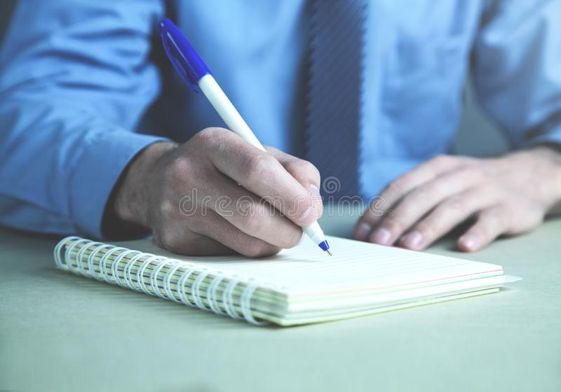 Businessman writing on notepad in the business desk. royalty free stock images