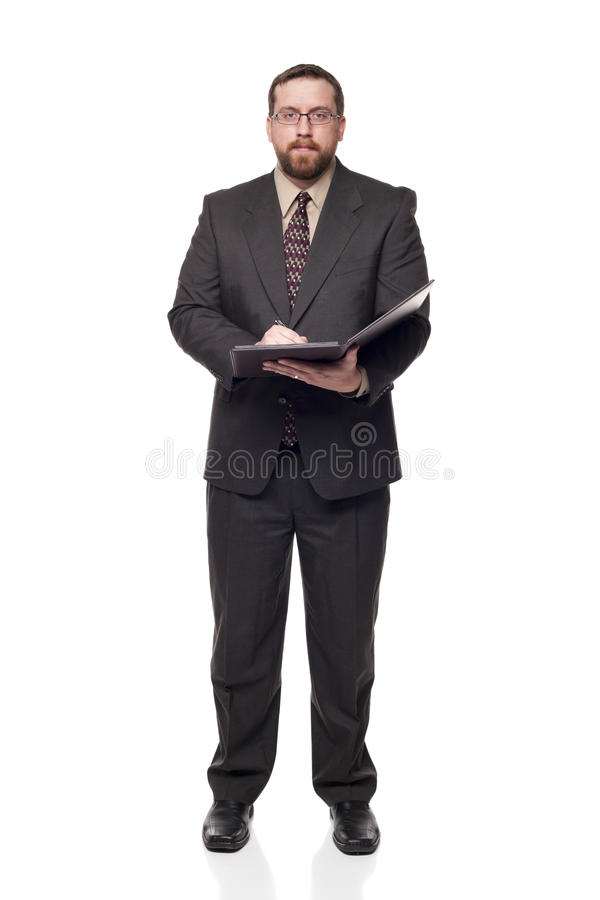 Businessman writing on notepad looking at c. Isolated full length studio shot of the front view of a businessman writing on notepad and looking at the camera royalty free stock images