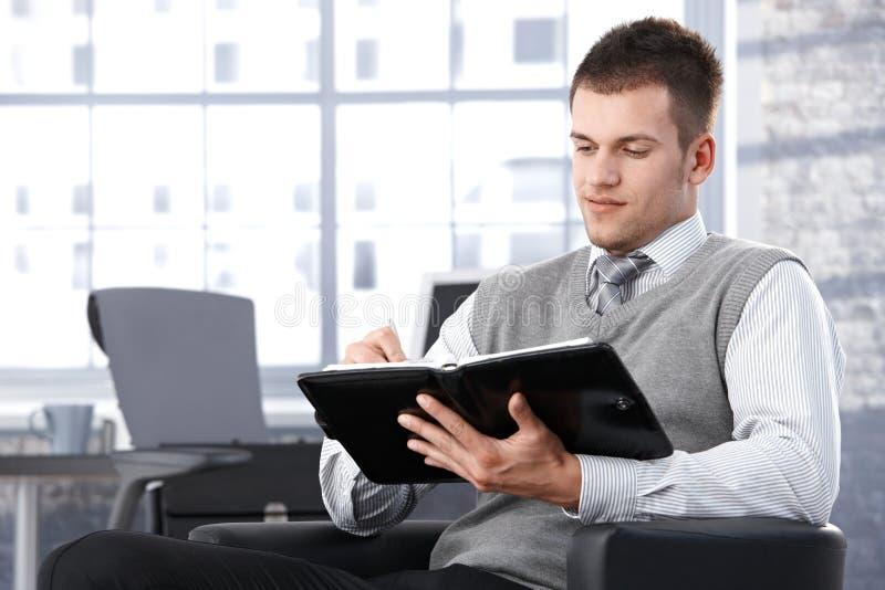 Businessman writing notes to personal organizer royalty free stock photos