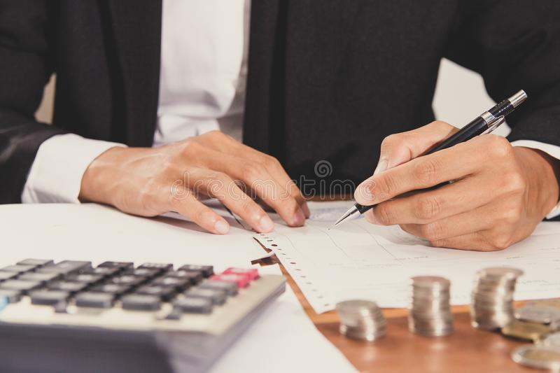 Businessman Writing paper and using calculator Calculating bonus retirement pay Or other compensation to employees to increase stock photos