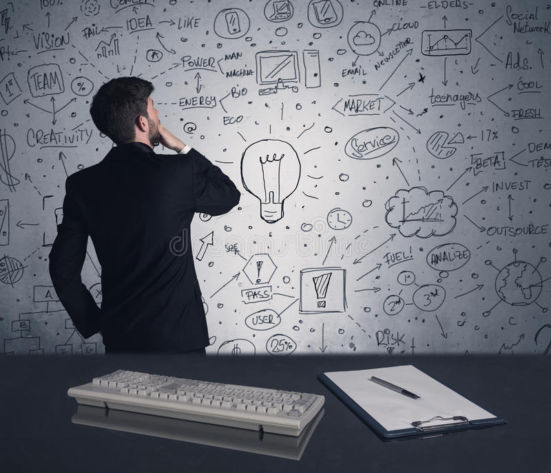 Businessman writing strategy plan on wall. An intelligent office worker drawing strategy ideas and future plan keywords on wall at a brainstorming meeting in royalty free stock photography