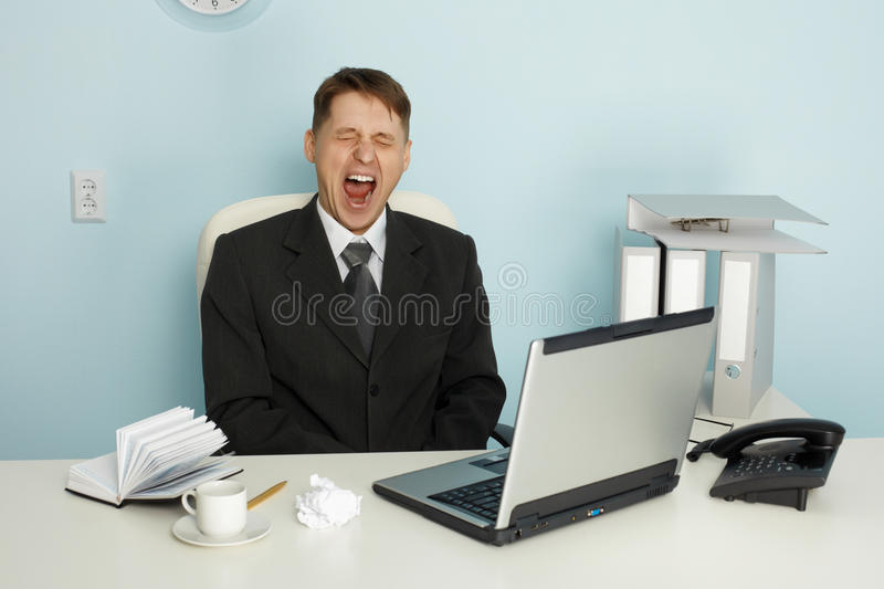 Businessman yawning from boredom and idleness. In the office stock images