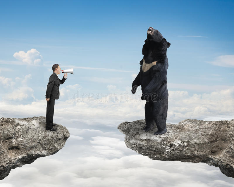 Businessman yelling at black bear on cliff with sky cloudscape. Businessman using megaphone yelling at black bear on cliff with sky cloudscape background stock image