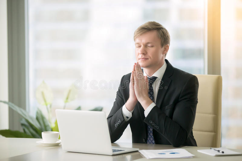 Businessman in yoga pose at the office desk stock photos