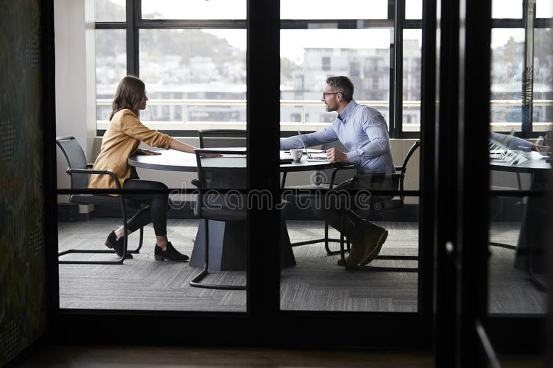 A businessman and young woman meeting for a job interview, full length, seen through glass wall. A businessman and young women meeting for a job interview, full royalty free stock photography