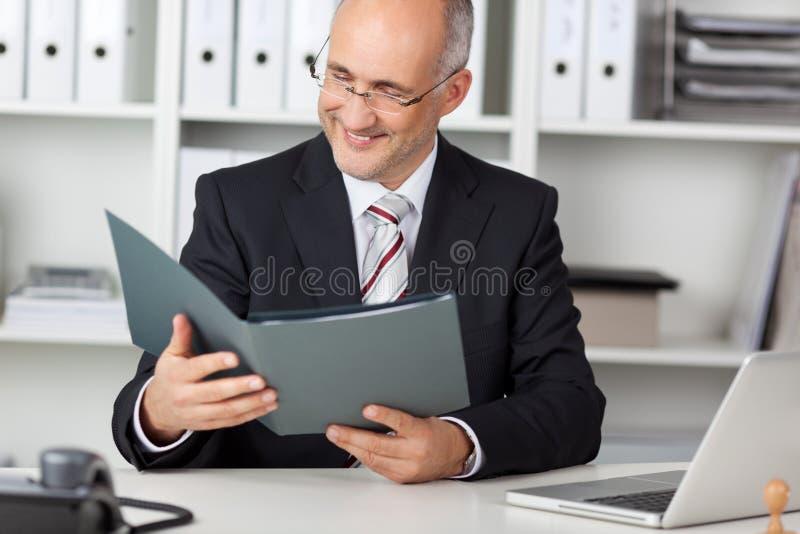 Businessmann de sorriso que olha o cv fotos de stock royalty free