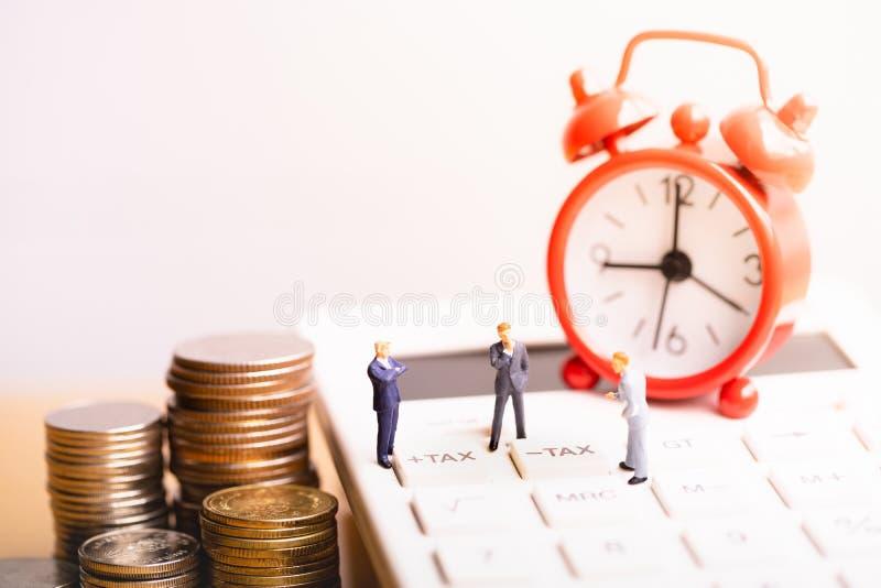 Businessmans和红色闹钟在计算器有词税的 纳税人记数器物产的 在不动产的税和 免版税图库摄影