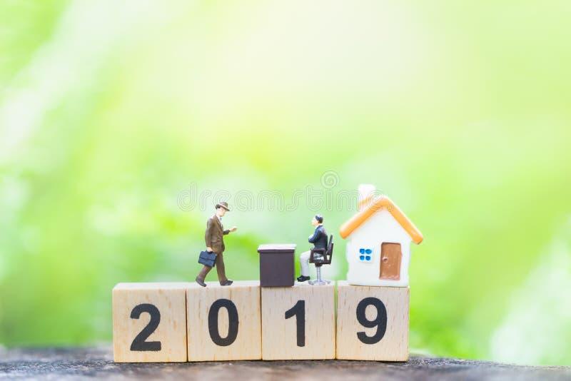 Businessmans e casa sull'anno di legno 2019 di numero di blocco sul fondo della natura della pianta immagini stock