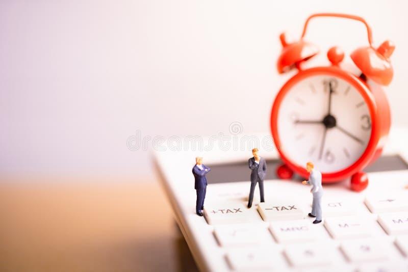 Businessmans et réveil rouge sur la calculatrice avec l'impôt de mot image stock