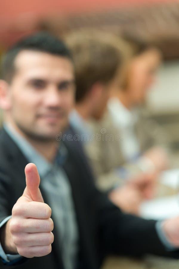 Businessmans kciuka pozytywnego gesta pierwszoplanowy ciało zamazywał w tle fotografia stock