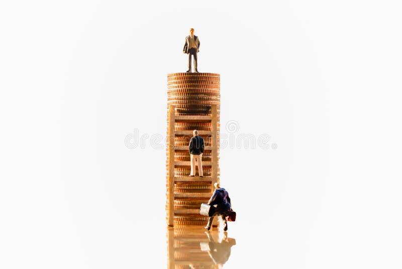 Businessmans sulla cima della pila delle monete Piano dei soldi di pensionamento e crescita di risparmio immagine stock