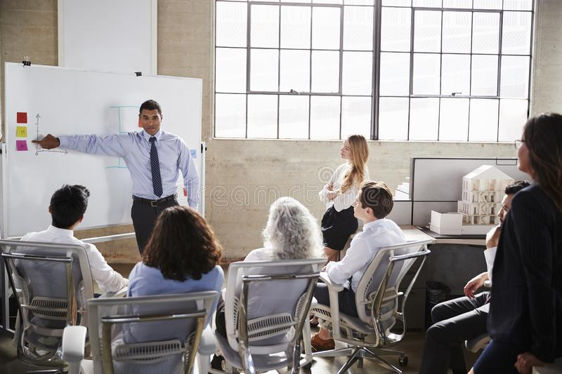 Businessmastands using whiteboard during a presentation royalty free stock photo