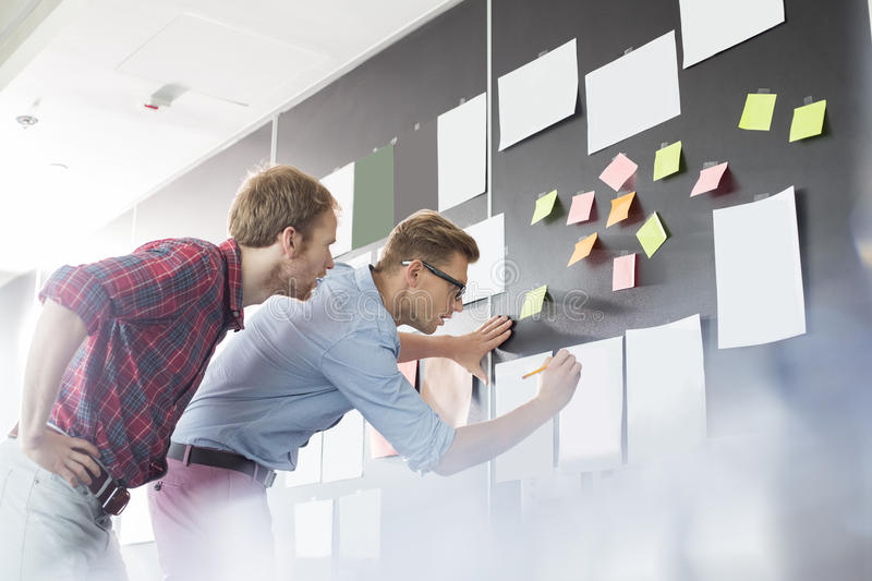 Businessmen analyzing documents on wall in office stock image