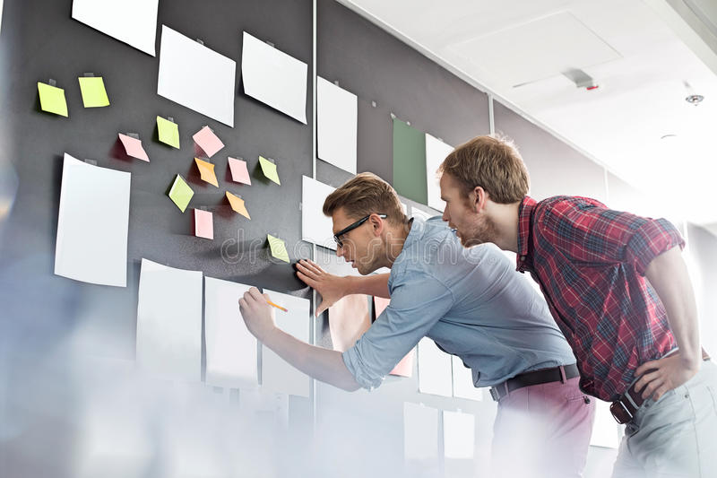 Businessmen analyzing documents on wall in office royalty free stock image