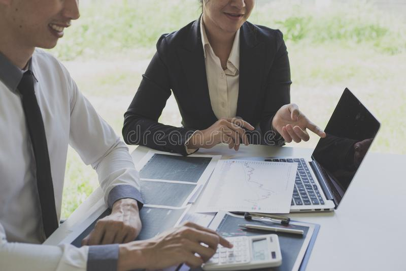 Businessmen are analyzing stock data, male company employees are discussing stock investment valuations, achieving business stock photo