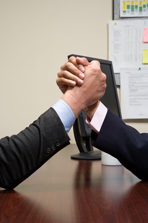 Businessmen arm wrestling stock images