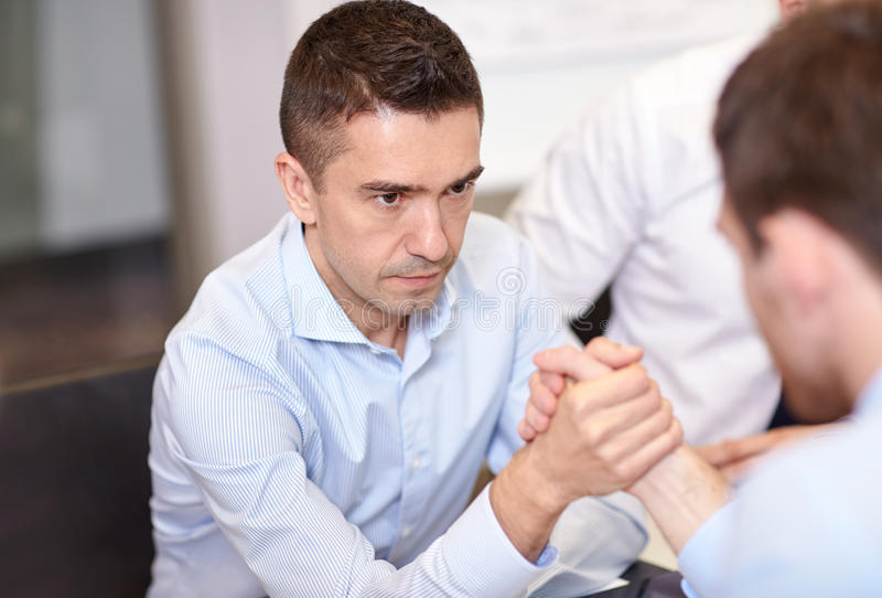 Businessmen arm wrestling in office. Business, people, crisis and confrontation concept - businessmen arm wrestling in office royalty free stock images