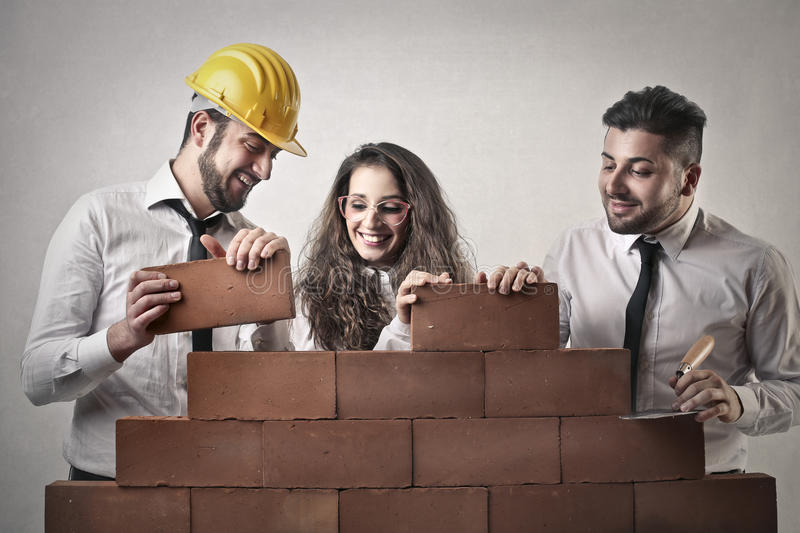 Businessmen and a business woman building a wall royalty free stock photos