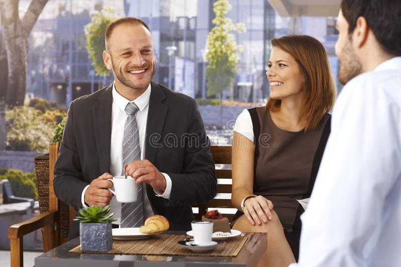 Businessmen and businesswoman relaxing at cafe stock photography