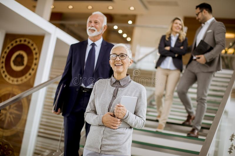 Businessmen and businesswomen walking and taking stairs in an of stock photo