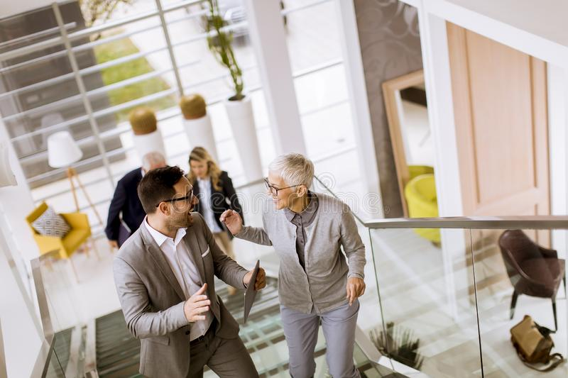 Businessmen and businesswomen walking and taking stairs in an of royalty free stock photos