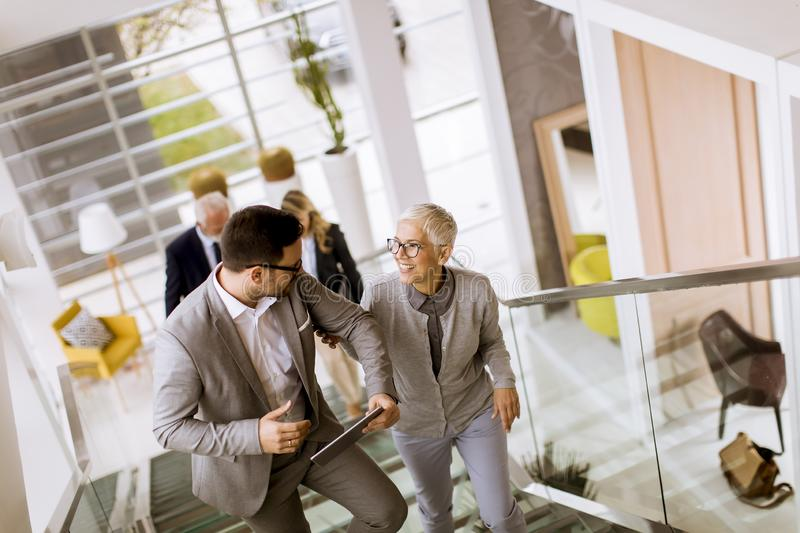 Businessmen and businesswomen walking and taking stairs in an of royalty free stock photography