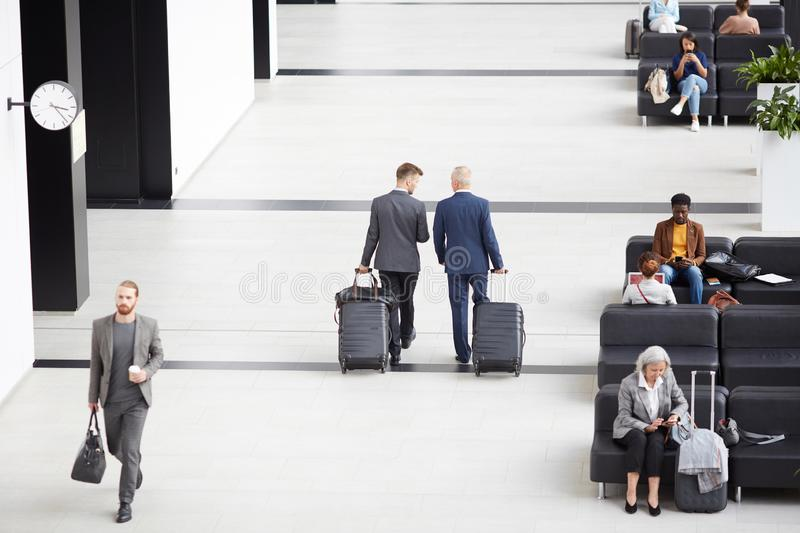 Businessmen carrying wheeled suitcases in airport stock photos