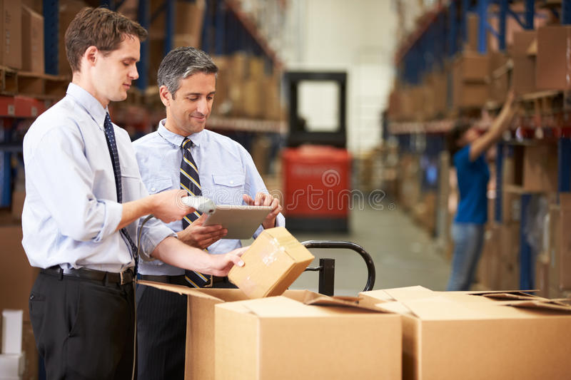 Businessmen Checking Boxes With Digital Tablet And Scanner royalty free stock photography