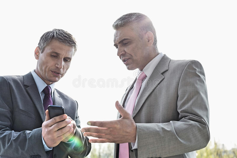 Businessmen discussing over mobile phone outdoors stock image
