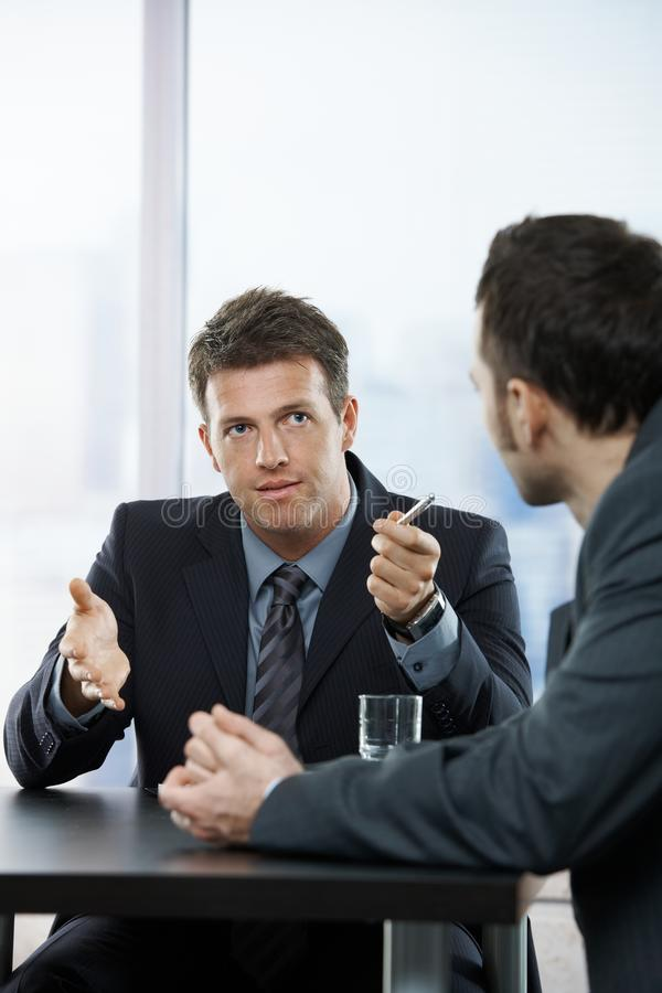 Businessmen at discussion. Two businessmen discussing tasks sitting at office table royalty free stock photo