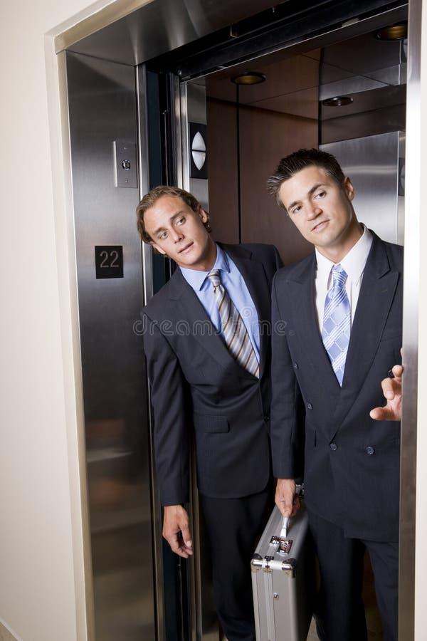Businessmen in elevator looking out doorway stock photography