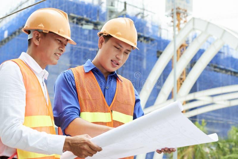 Businessmen examining blueprint in team royalty free stock photos