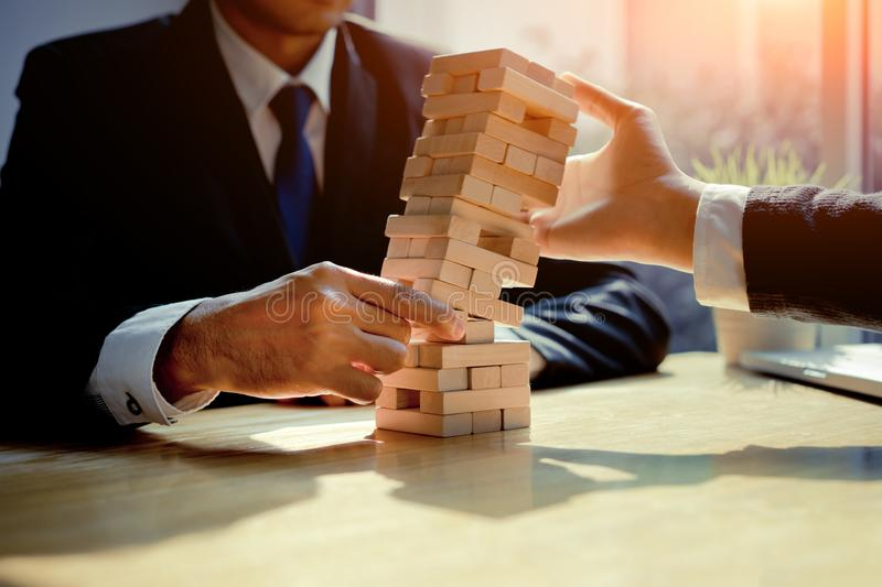 Businessmen fail danger tower challenge game. Building consturction protect plan and project for control risk shape with hand block royalty free stock photography